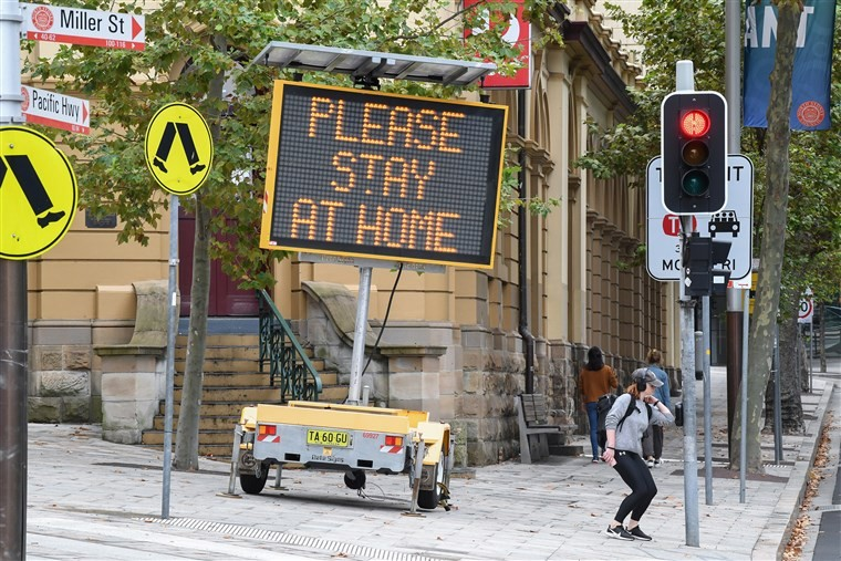 """Electronic road sign saying """"please stay at home"""""""