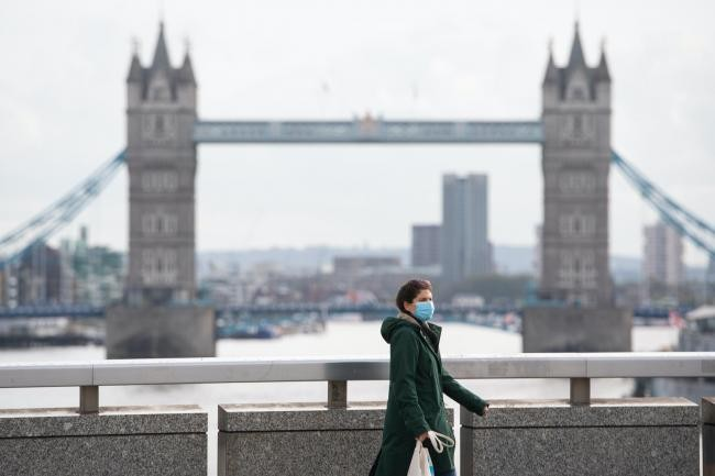 View of Tower Bridge from London Bridge with a lady in a facemask walking by